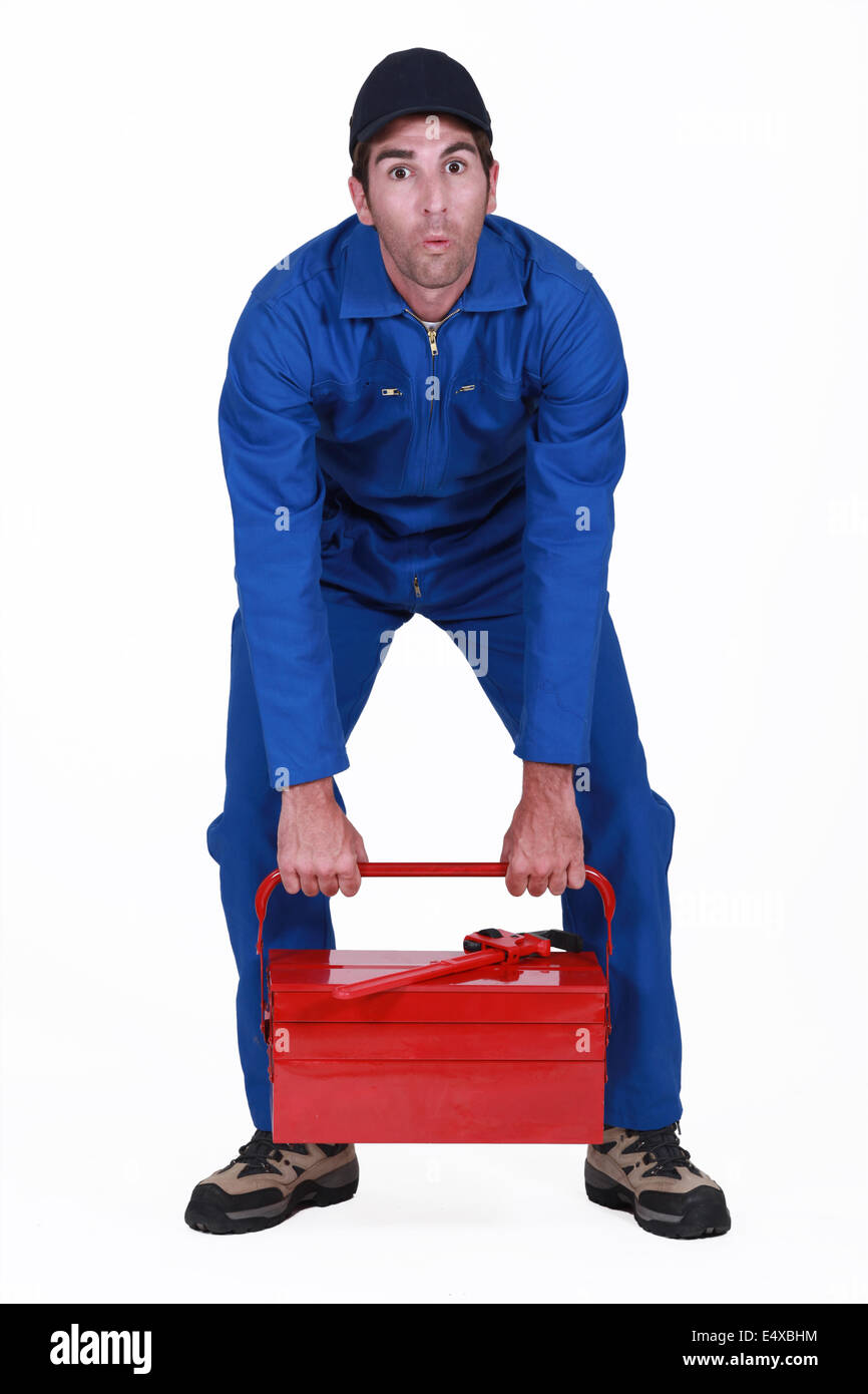 Man struggling to lift tool box - Stock Image