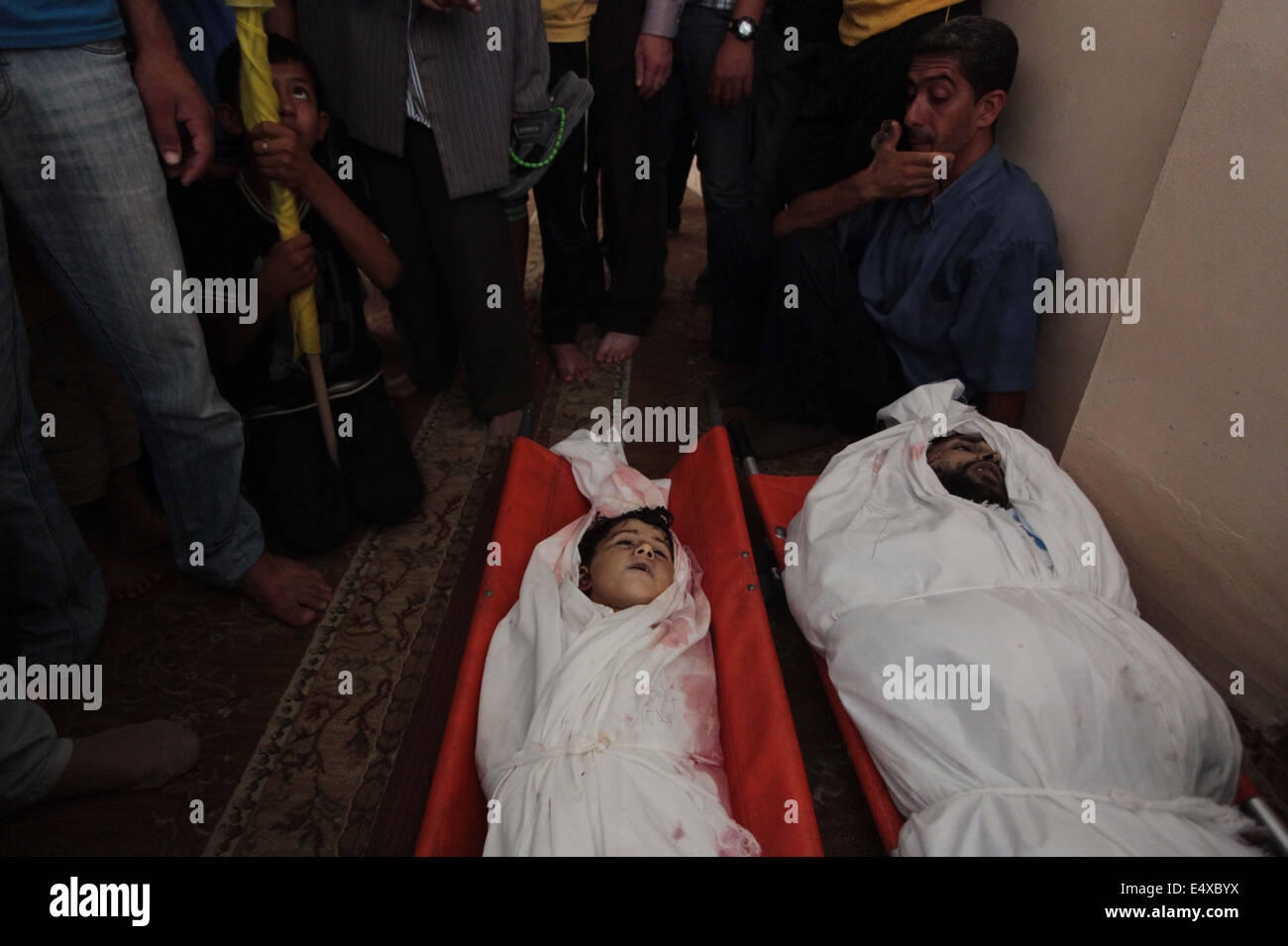 Khan Younis, Gaza Strip, Palestinian Territory. 17th July, 2014. Palestinian mourners and family members mourn over - Stock Image