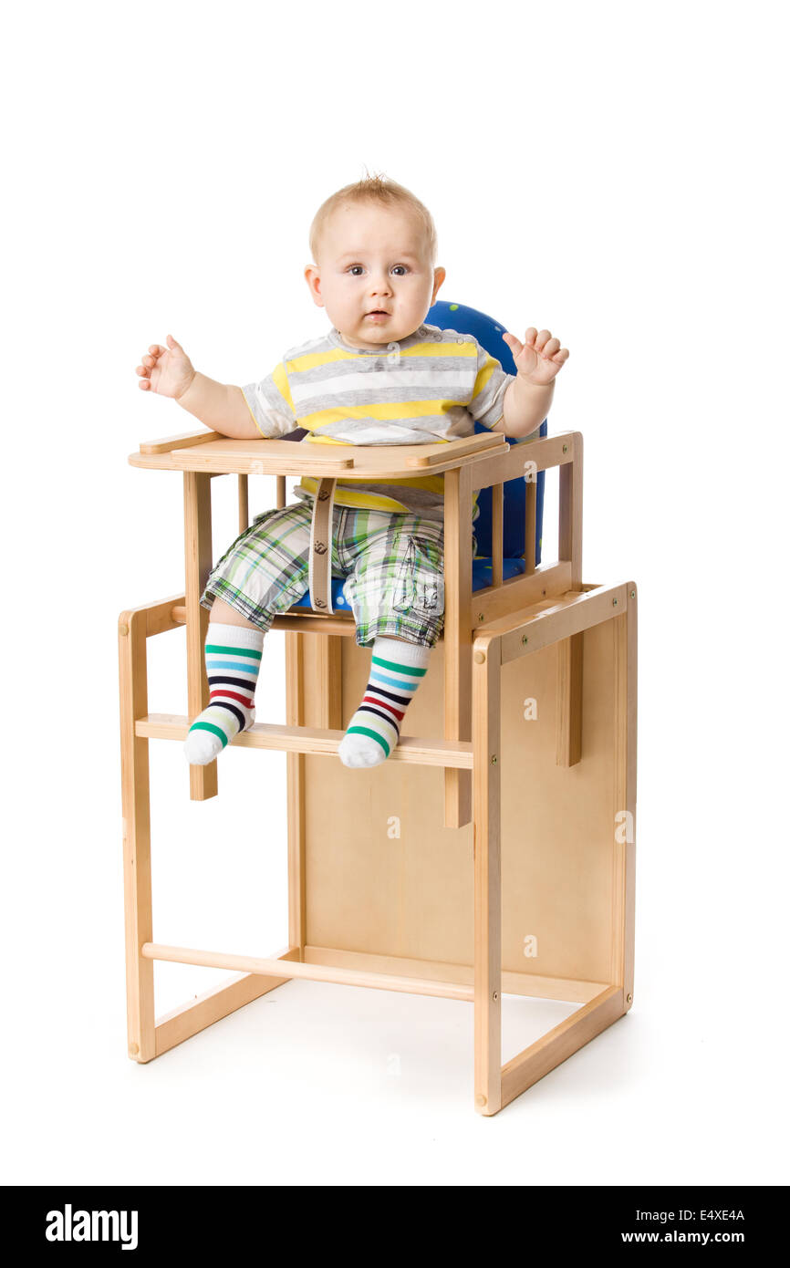 Baby sitting in highchair. - Stock Image