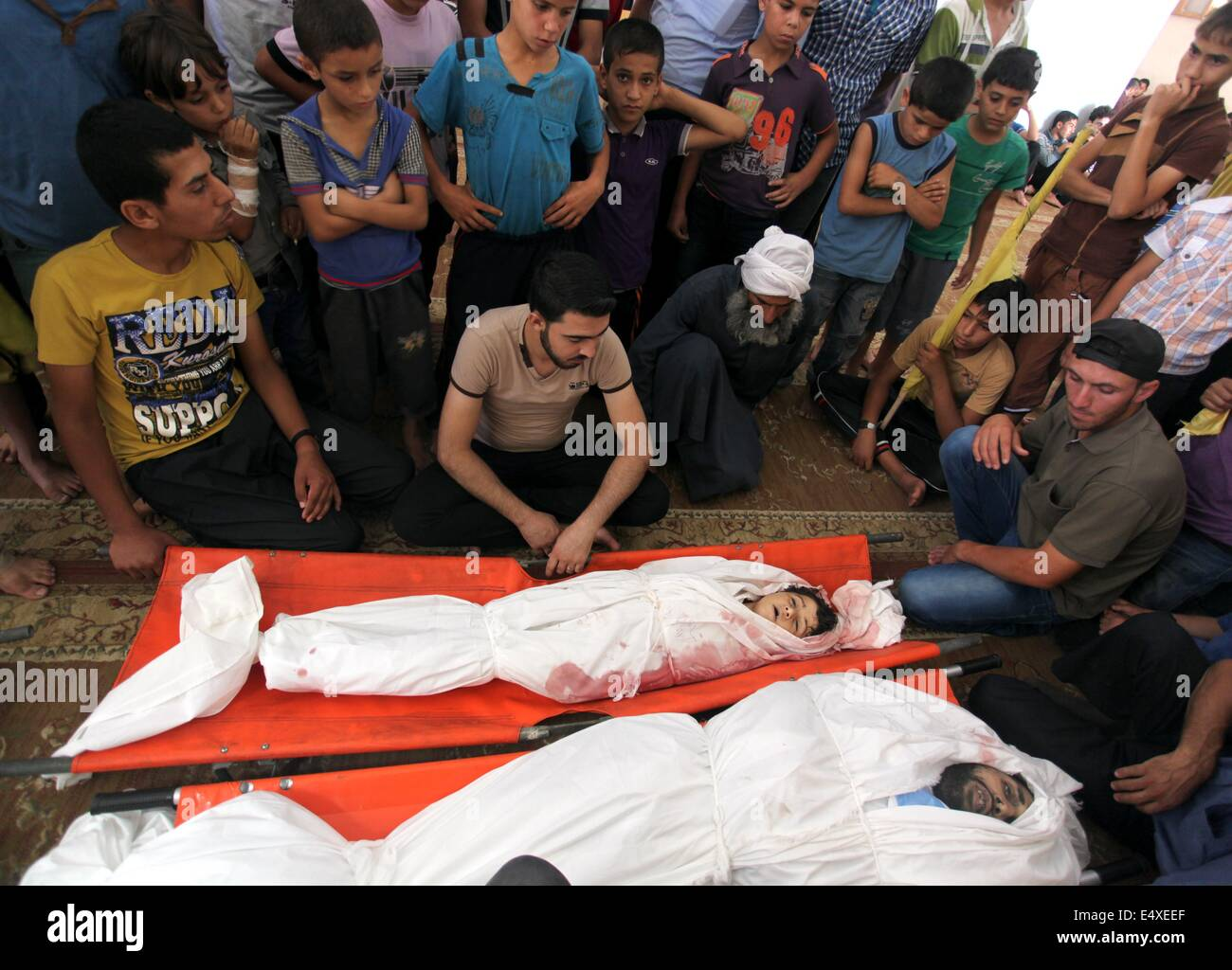Khan Younis, Gaza Strip, Palestinian Territory. 17th July, 2014. Palestinian mourners mourn over the bodies of four - Stock Image