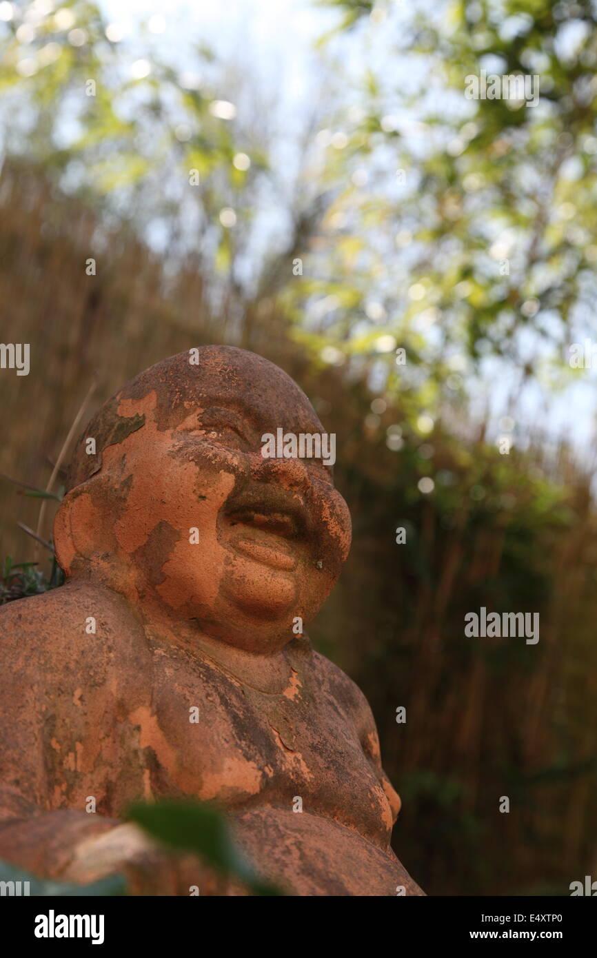 Smiling Buddha statue - Stock Image