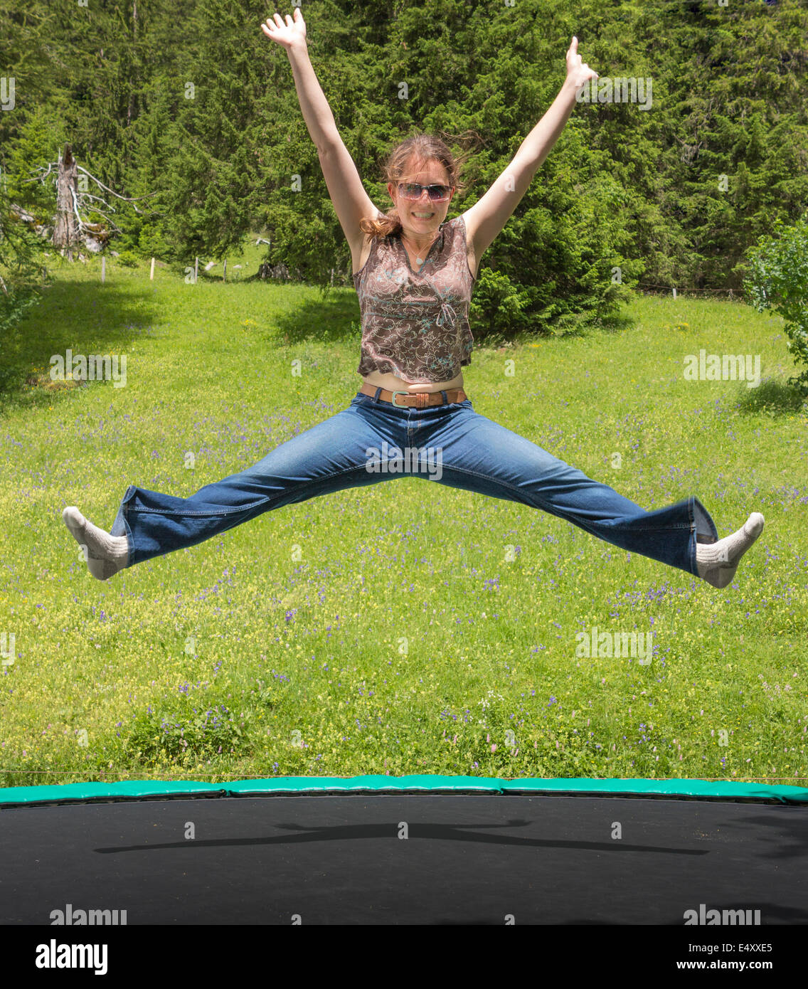 A young woman bouncing with joy on a trampoline in a mountain setting - Stock Image