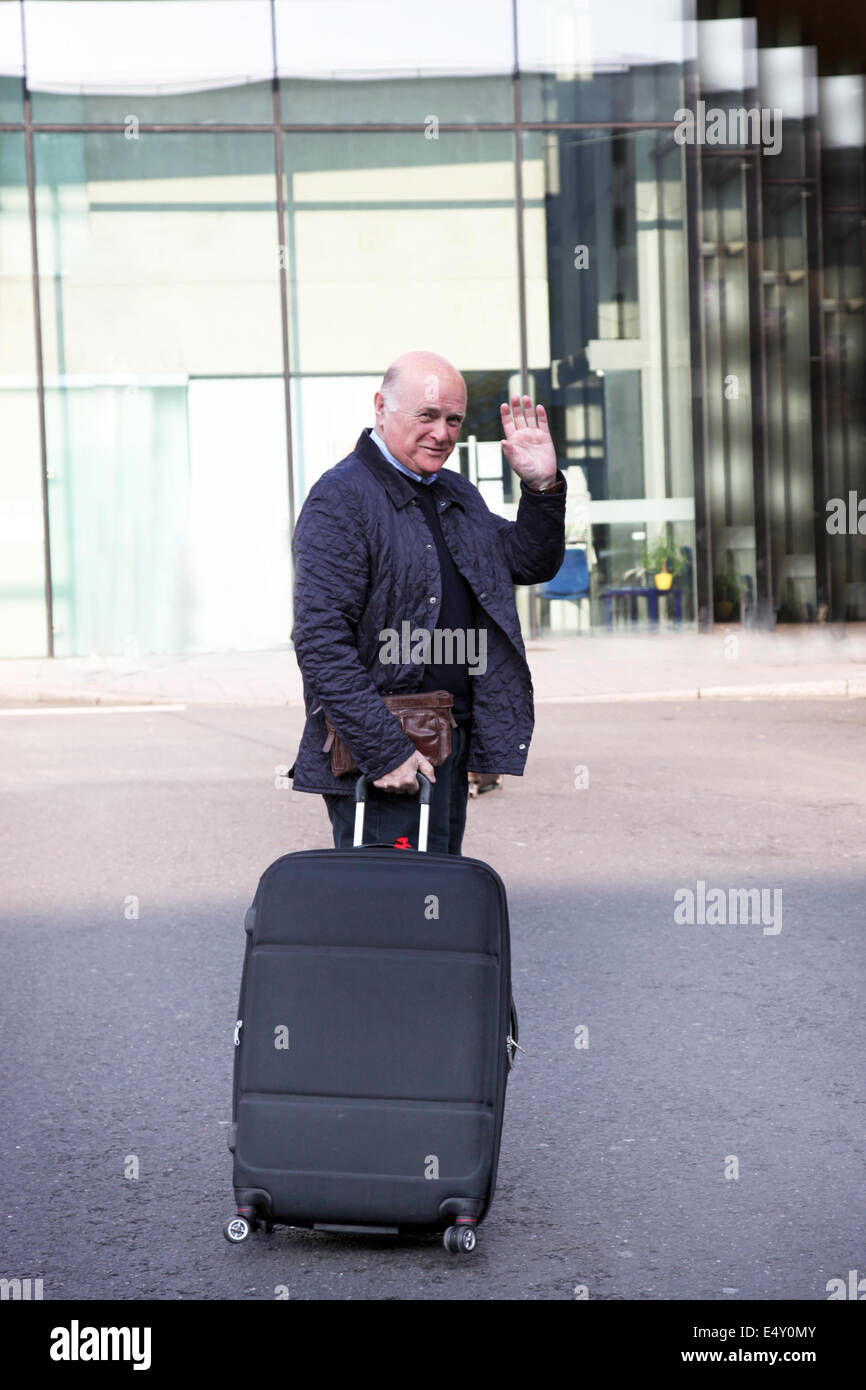 Elderly man waving goodbye - Stock Image