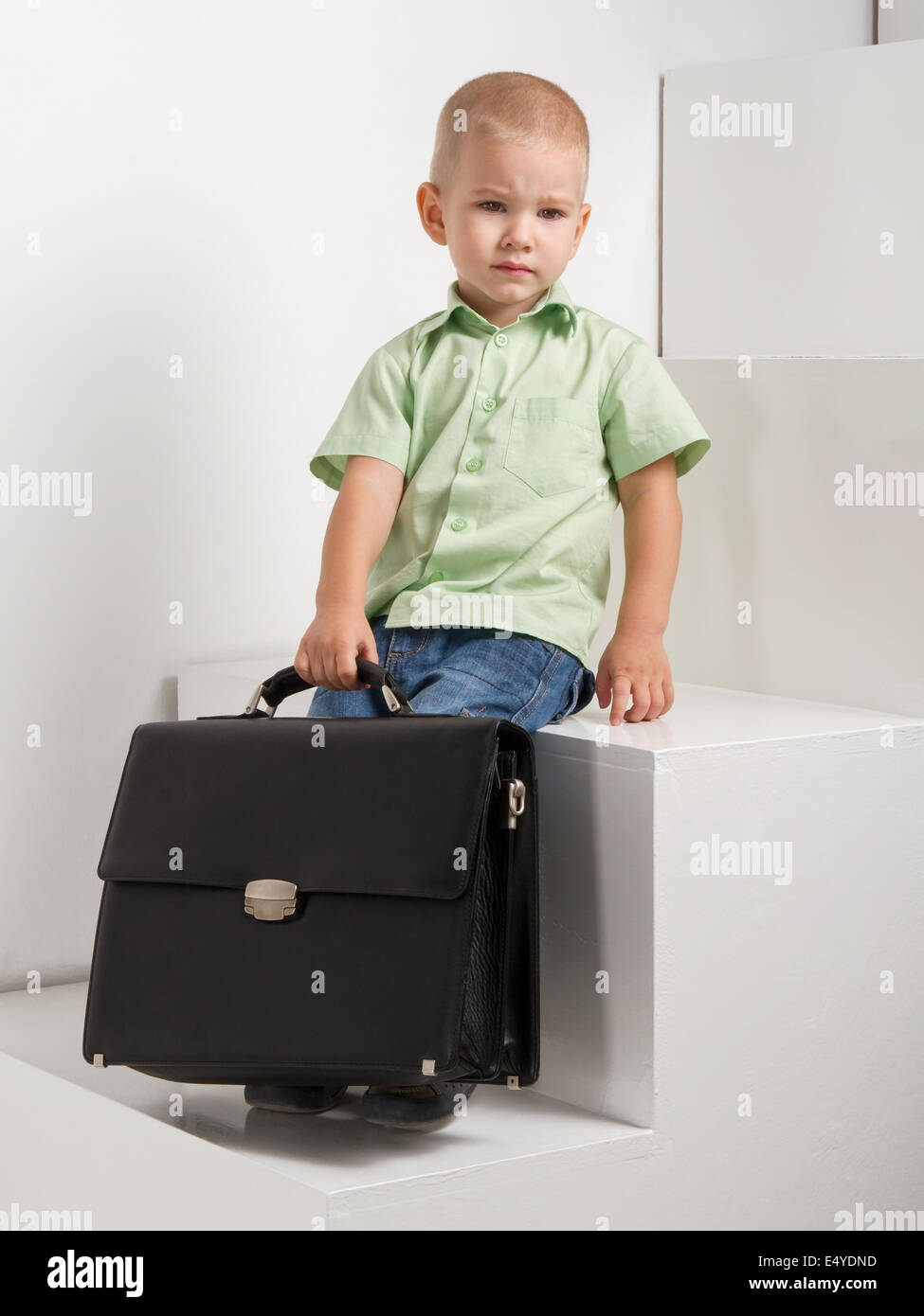 sad kid with briefcase on stairs on light background - Stock Image