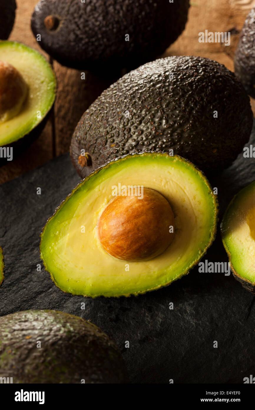 Organic Raw Green Avocados Sliced in Half - Stock Image