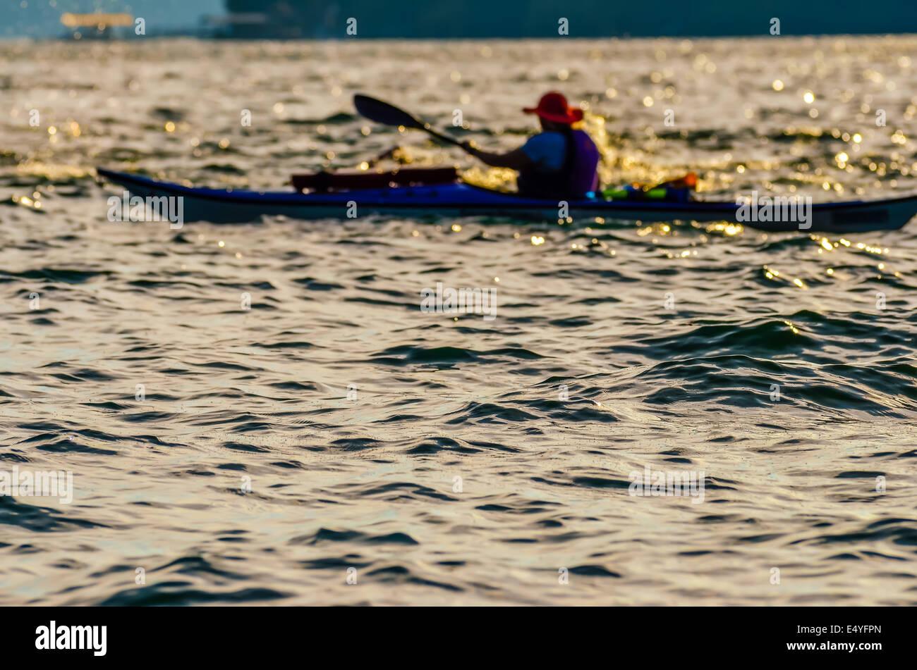 Sillouette of man kayaking on lake - Stock Image