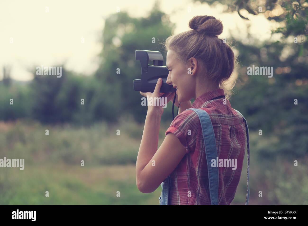 Girl photographer shooting outdoors - Stock Image