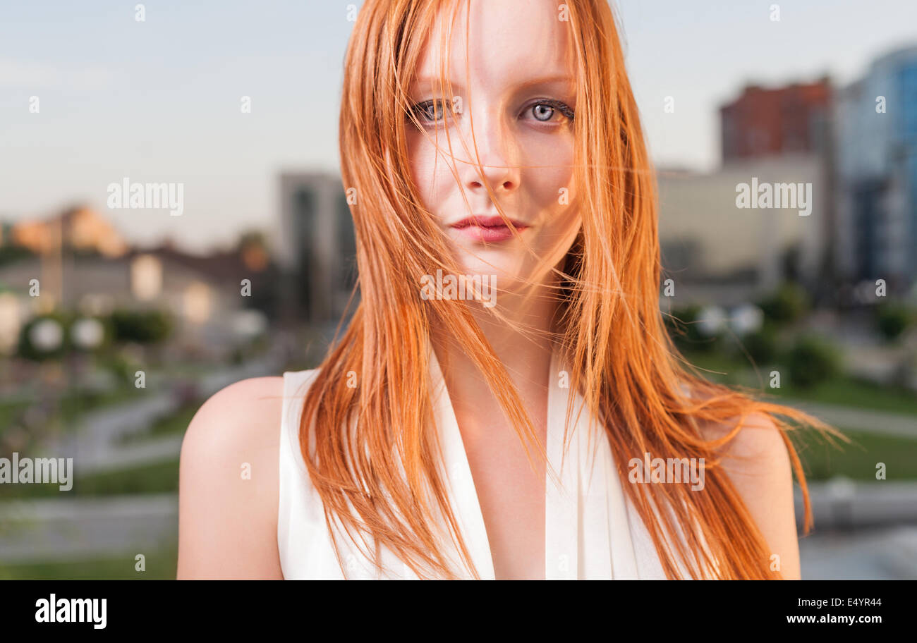 Portrait of freckled young woman cityscape - Stock Image