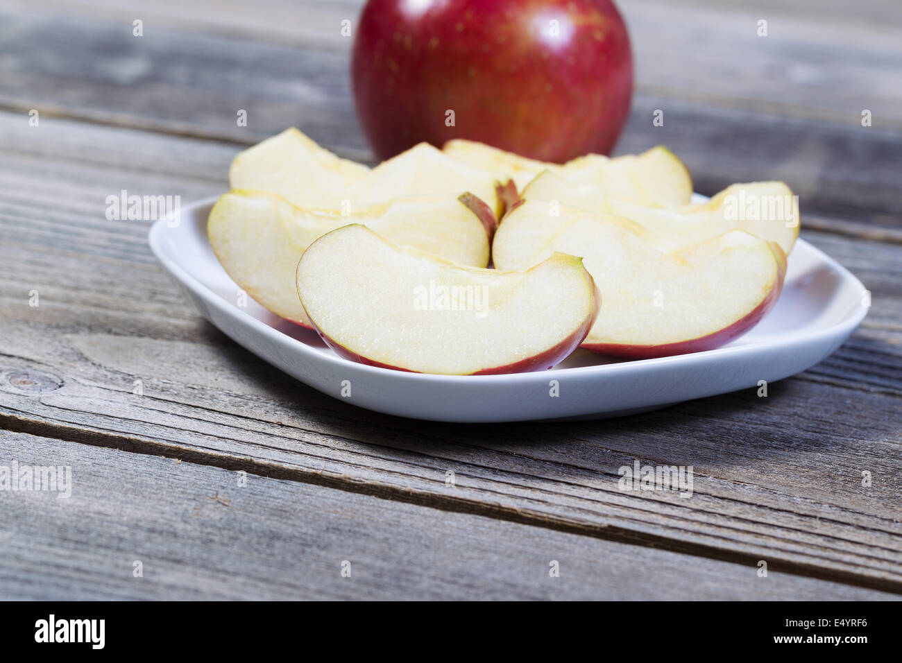Horizontal photo of fresh apple slices, on white plate, with whole apple and rustic wood in background - Stock Image
