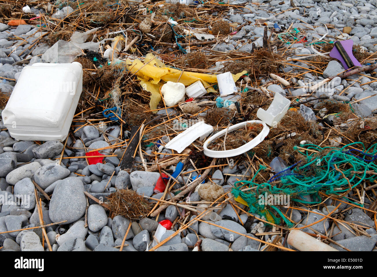 flotsam on the beach, a mixture of plastic and old rope and debris washed up by the sea - Stock Image