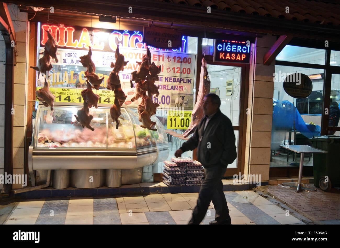 Passerby walks near meat shop, Konya, Turkey - Stock Image