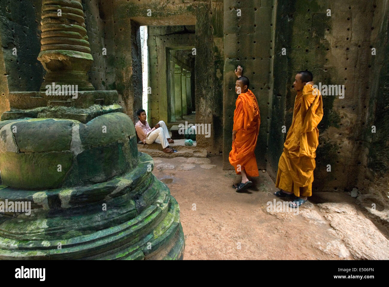 Two Buddhist monks in the inner part of the Temple Preah Khan.  Little is known about the history of Preah Khan. - Stock Image
