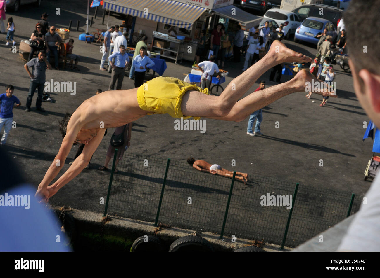 A Turkish youth dives from the handrail of Galata bridge into the waters of the Golden Horn several meters below - Stock Image