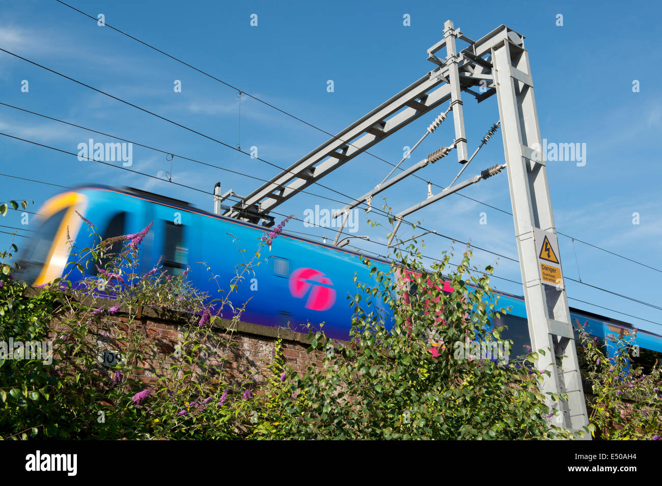 A First TransPennine ADtranz / Bombardier Express Class 170 Turbostar runs along an electrified rail line in Manchester. - Stock Image