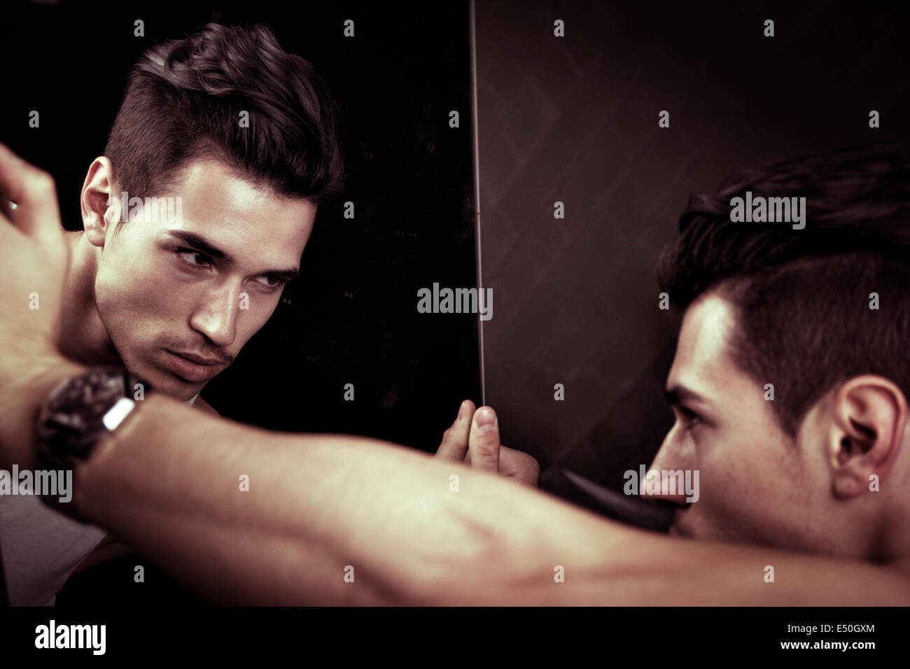 Narcissistic handsome young man leaning forwards admiring his reflection in the mirror in a show of self-absorption - Stock Image