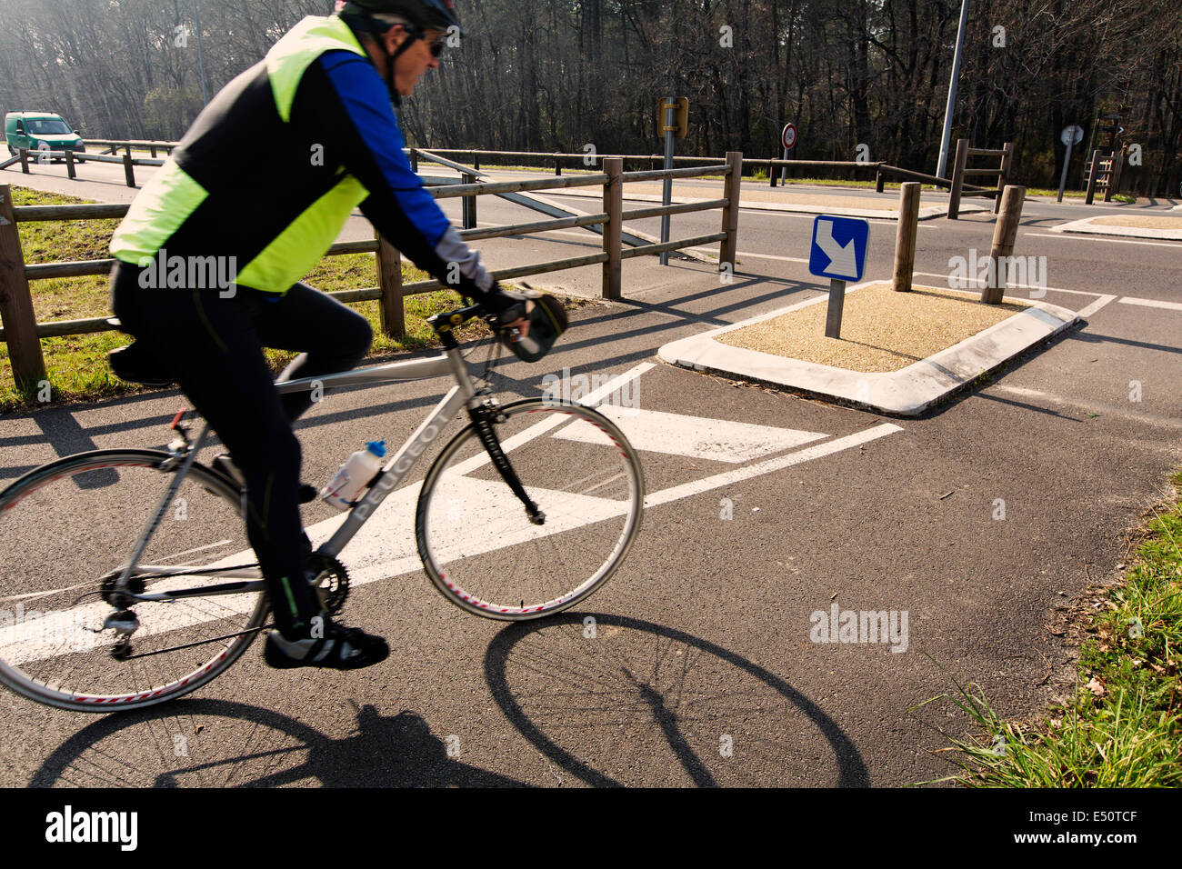 Cyclist on a road crossing in Gironde Landes Aquitaine France Stock Photo