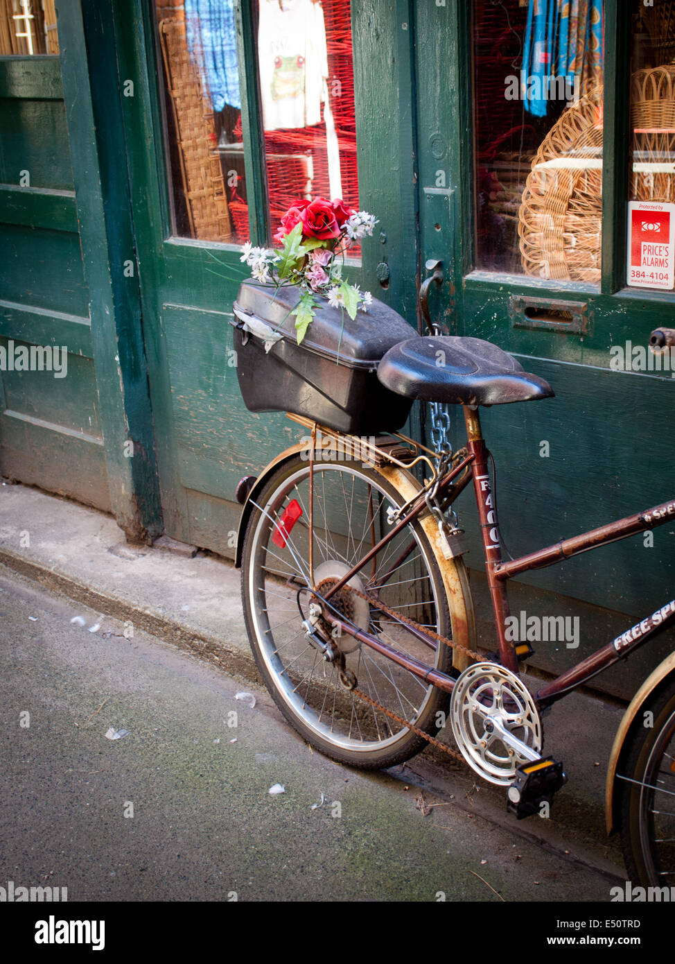 A city bicycle with flowers in the back parked in Fan Tan Alley in Victoria, British Columbia, Canada. - Stock Image