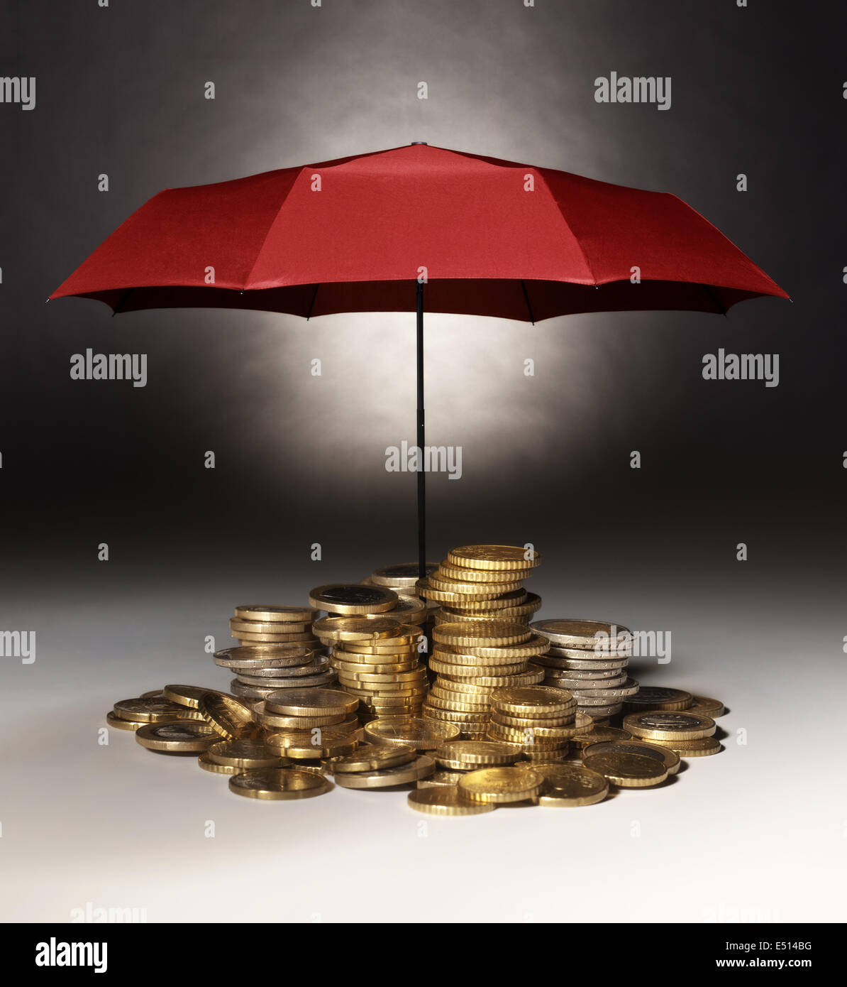 Coins with red protective umbrella - Stock Image