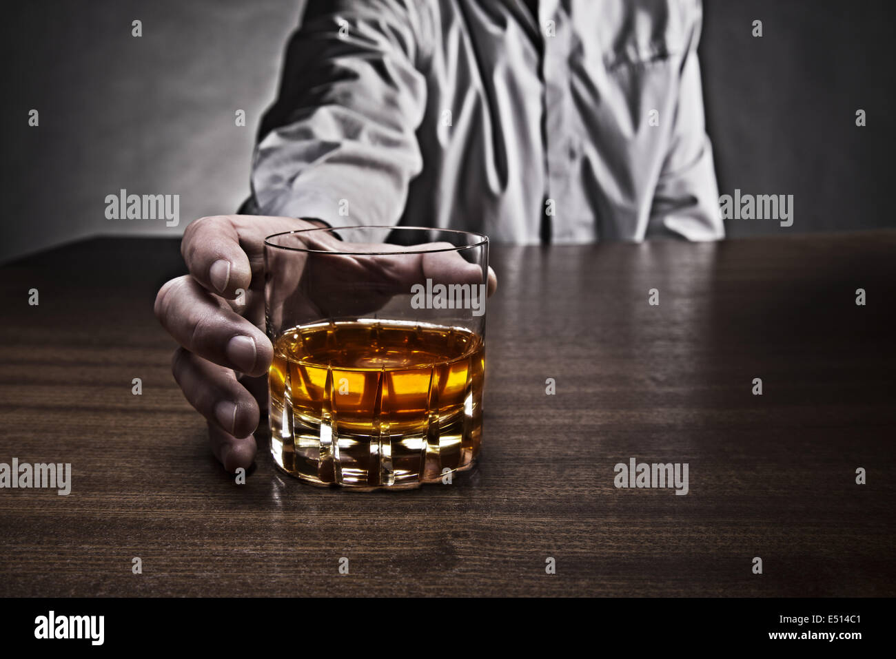 Man grabs a glass of whiskey - Stock Image