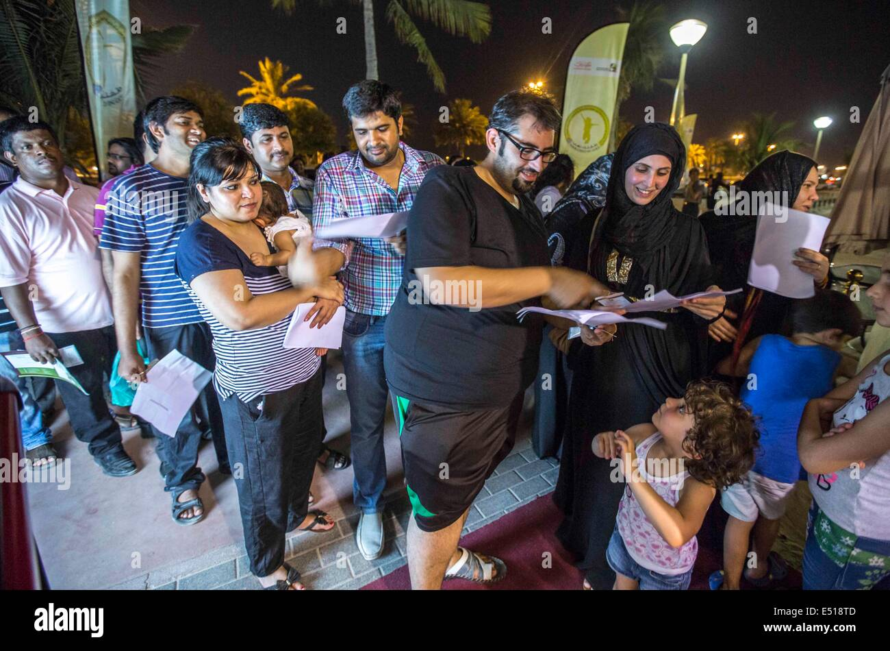 """Dubai, United Arab Emirates. 17th July, 2014. People line up to register their respective weights for a """"lose weight Stock Photo"""
