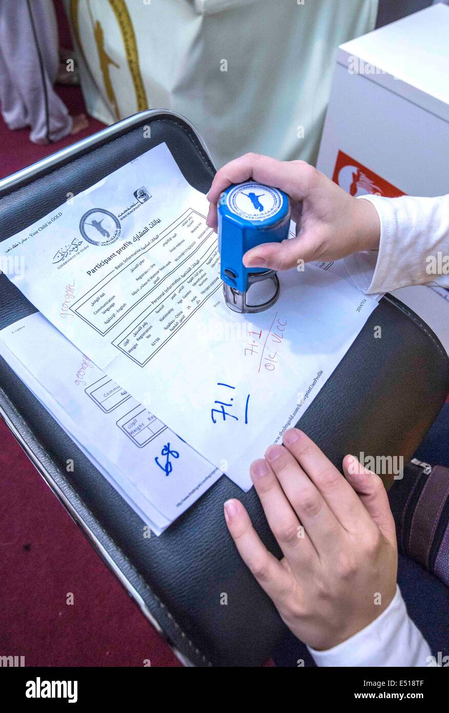 """Dubai, United Arab Emirates. 17th July, 2014. A staff member stamps on an application for a """"lose weight - win gold"""" Stock Photo"""