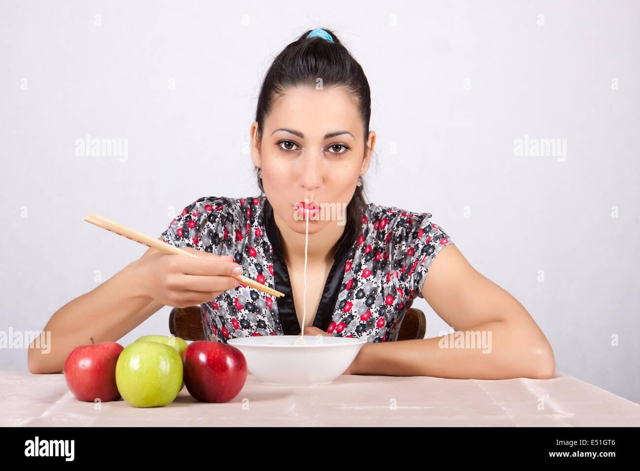 Woman eat noodles - Stock Image
