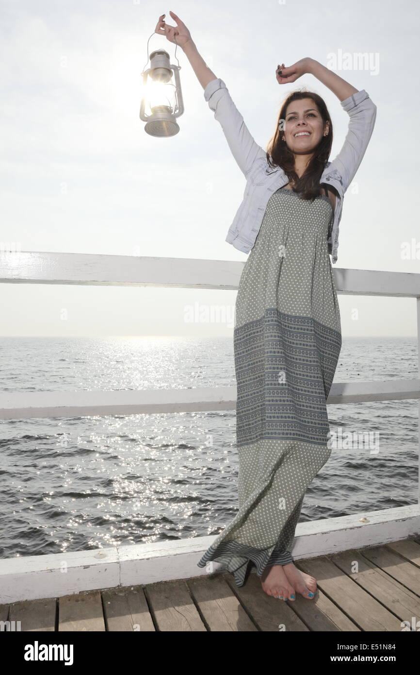 Girl on pier with kerosene lamp - Stock Image