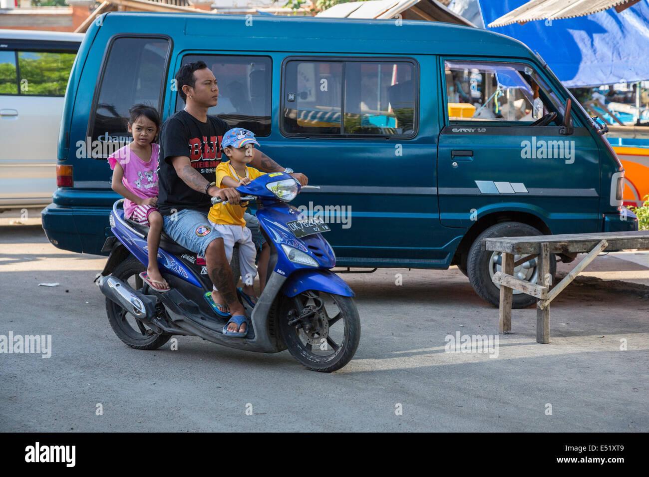 Jimbaran, Bali, Indonesia.  Father and Children on Motorbike, no Helmets. - Stock Image