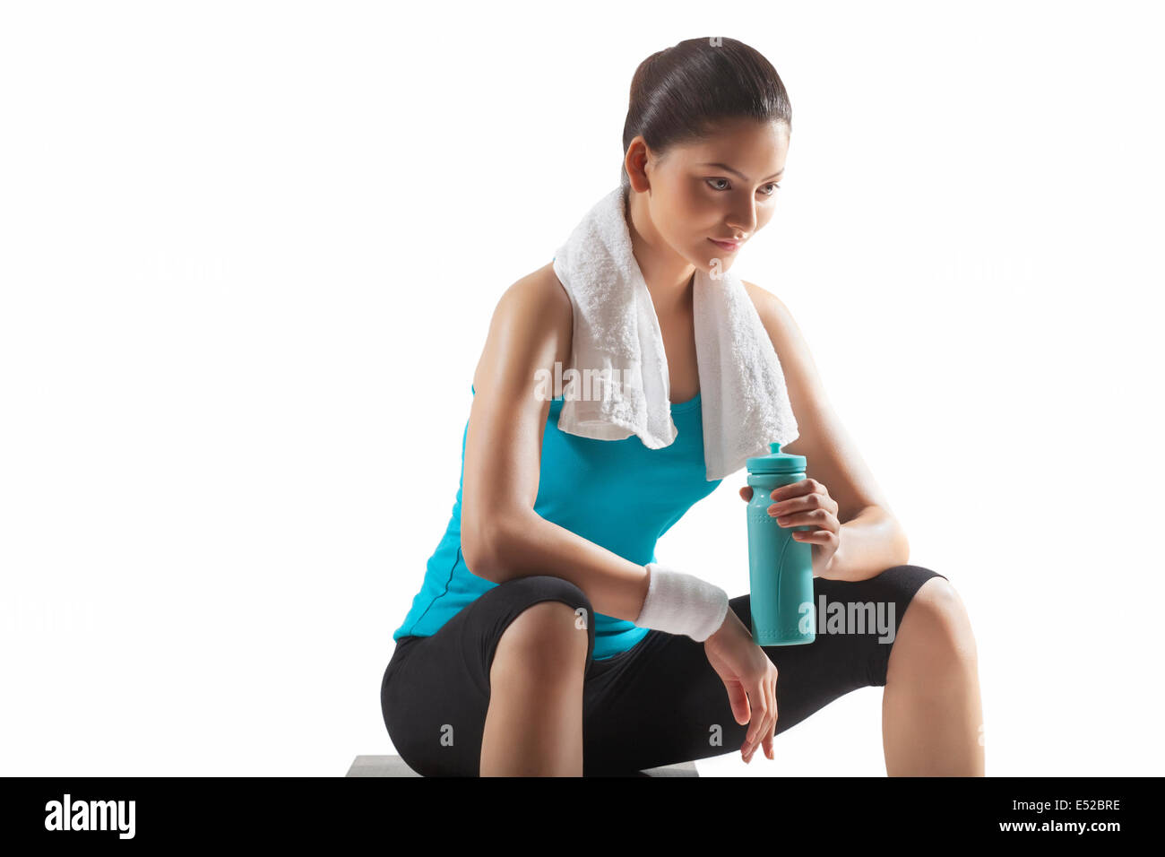 Fit young woman holding water bottle isolated over white background - Stock Image