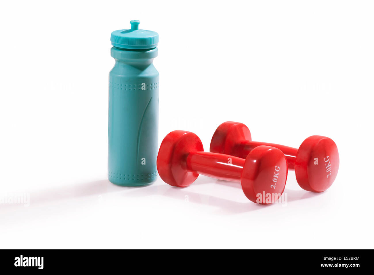 Red dumbbells and water bottle isolated over white background - Stock Image