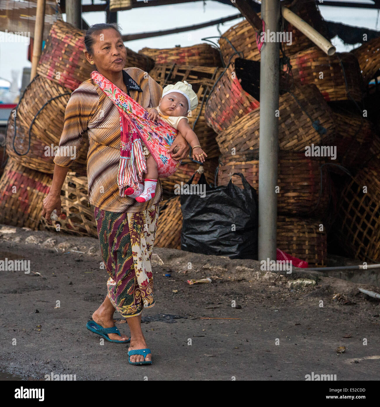 Bali, Indonesia.  Woman Carrying Baby in a Shoulder-sling.  Jimbaran. - Stock Image