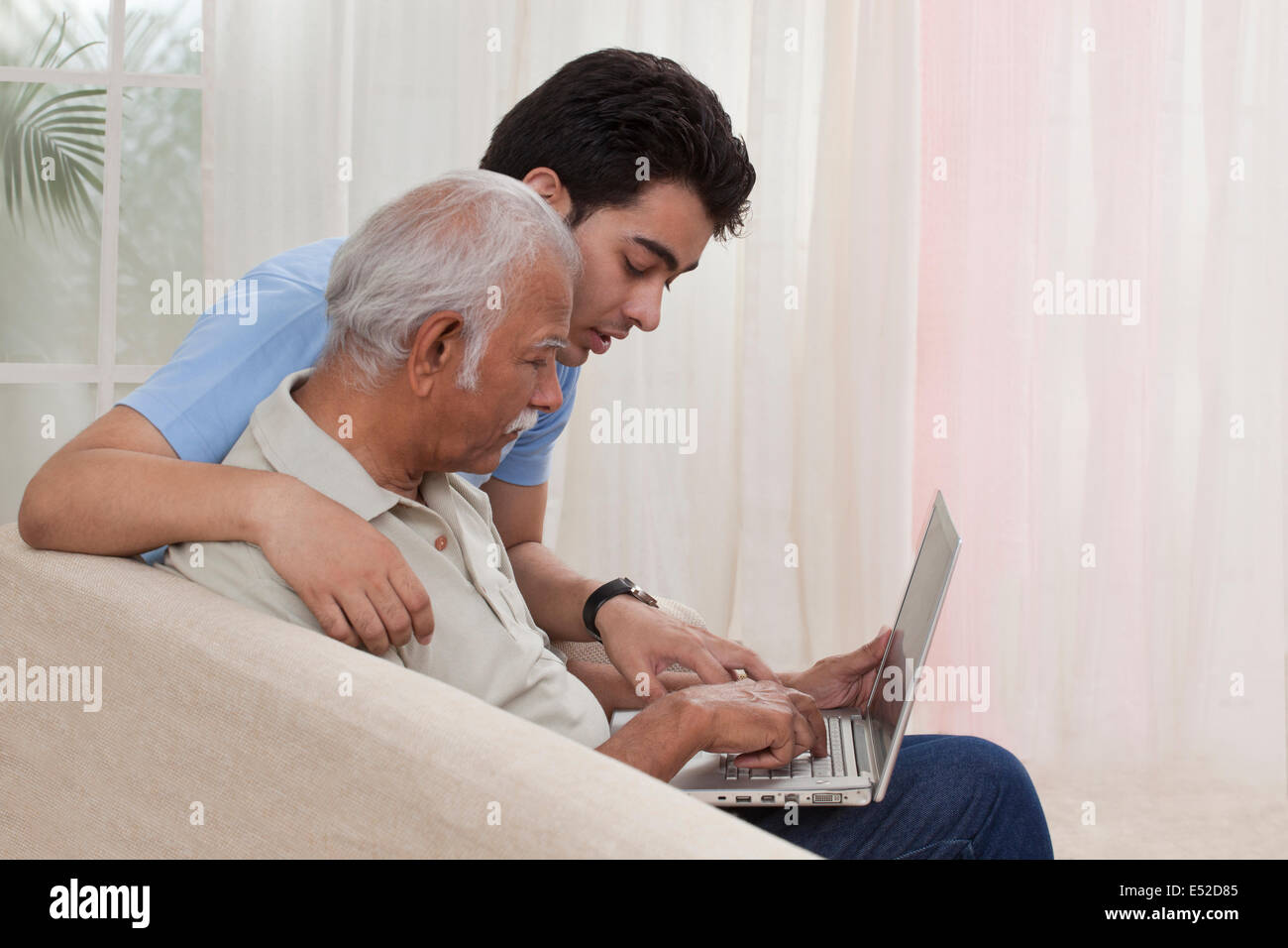 Grandson teaching grandfather how to operate laptop - Stock Image