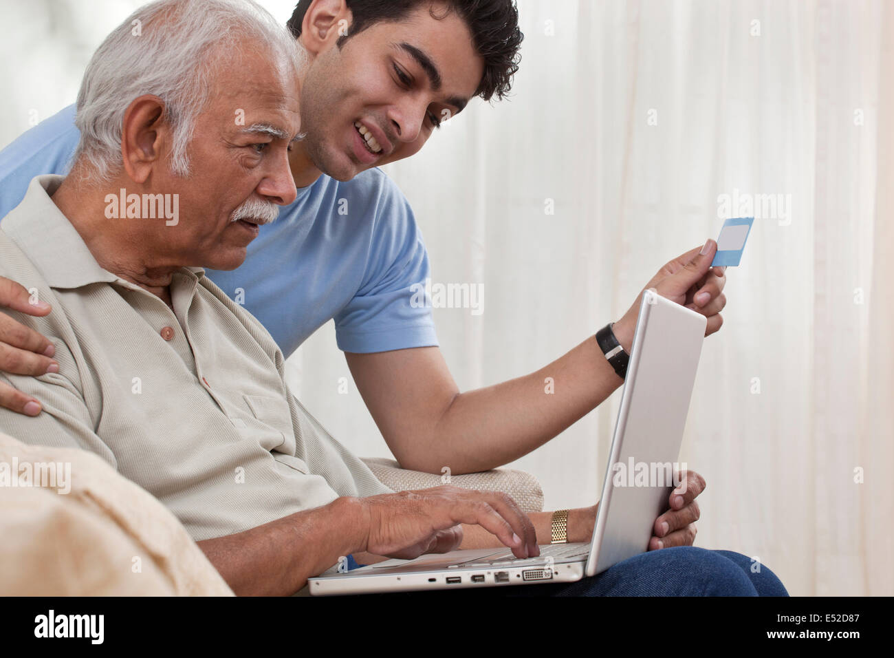 Grandson teaching grandfather how to operate laptop Stock Photo