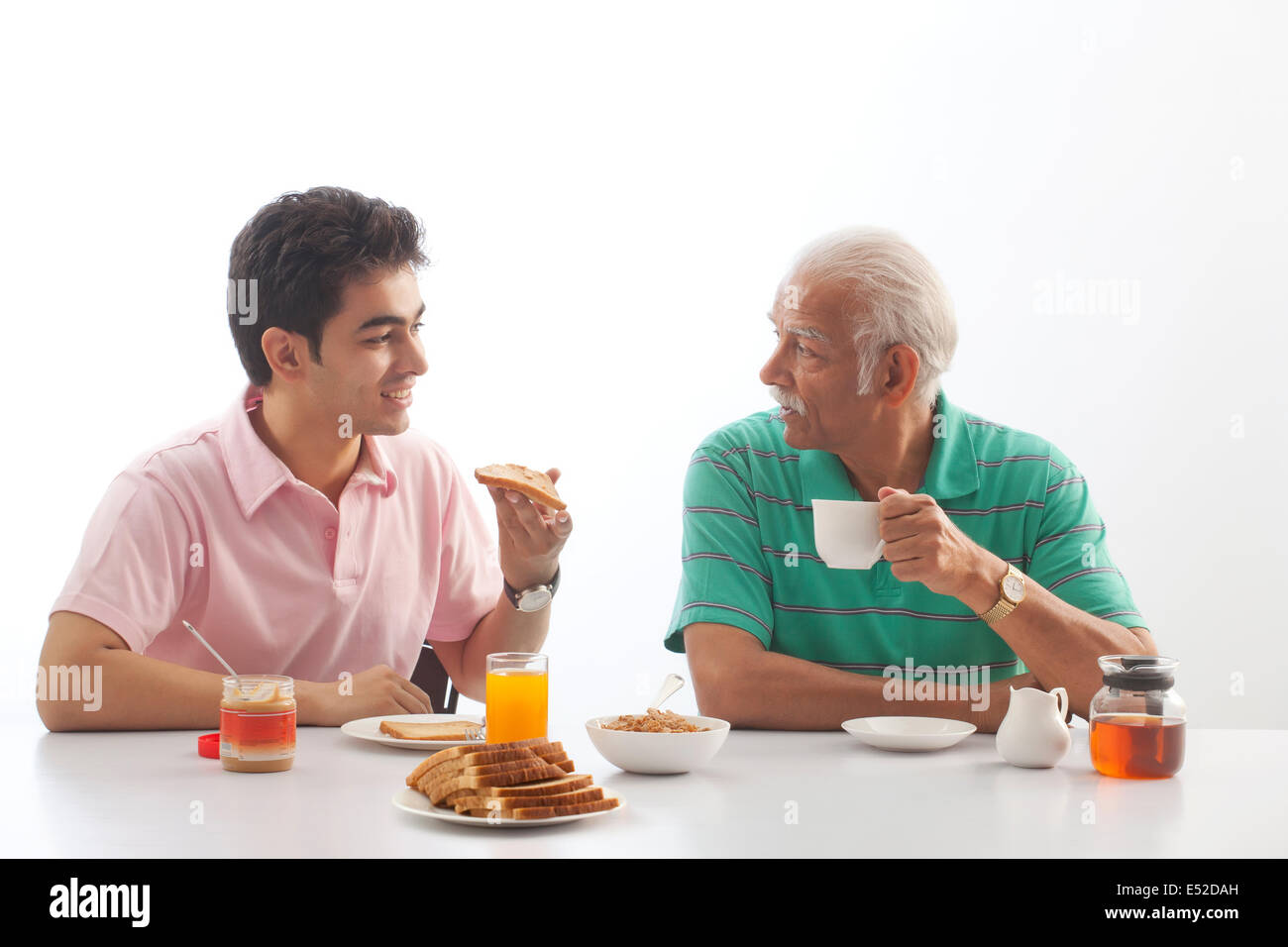 Grandfather and grandson eating breakfast - Stock Image