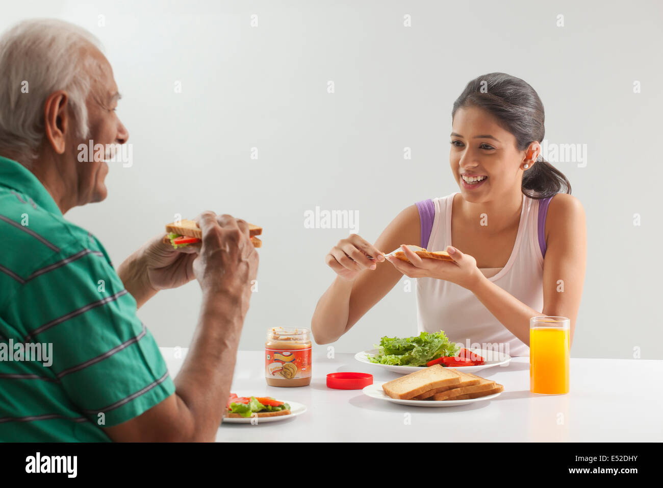 Grandfather and granddaughter eating breakfast - Stock Image