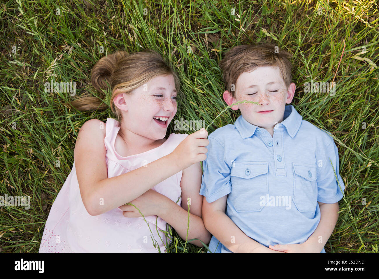 Two children, brother and sister lying side by side on the grass - Stock Image