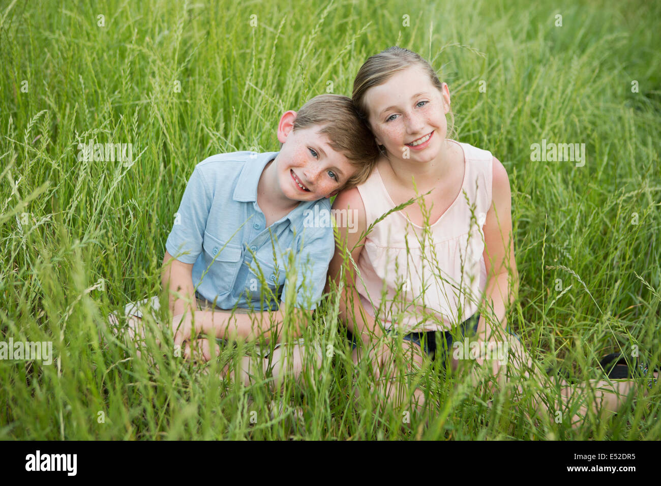 Brother and sister sitting side by side, in long grass. - Stock Image