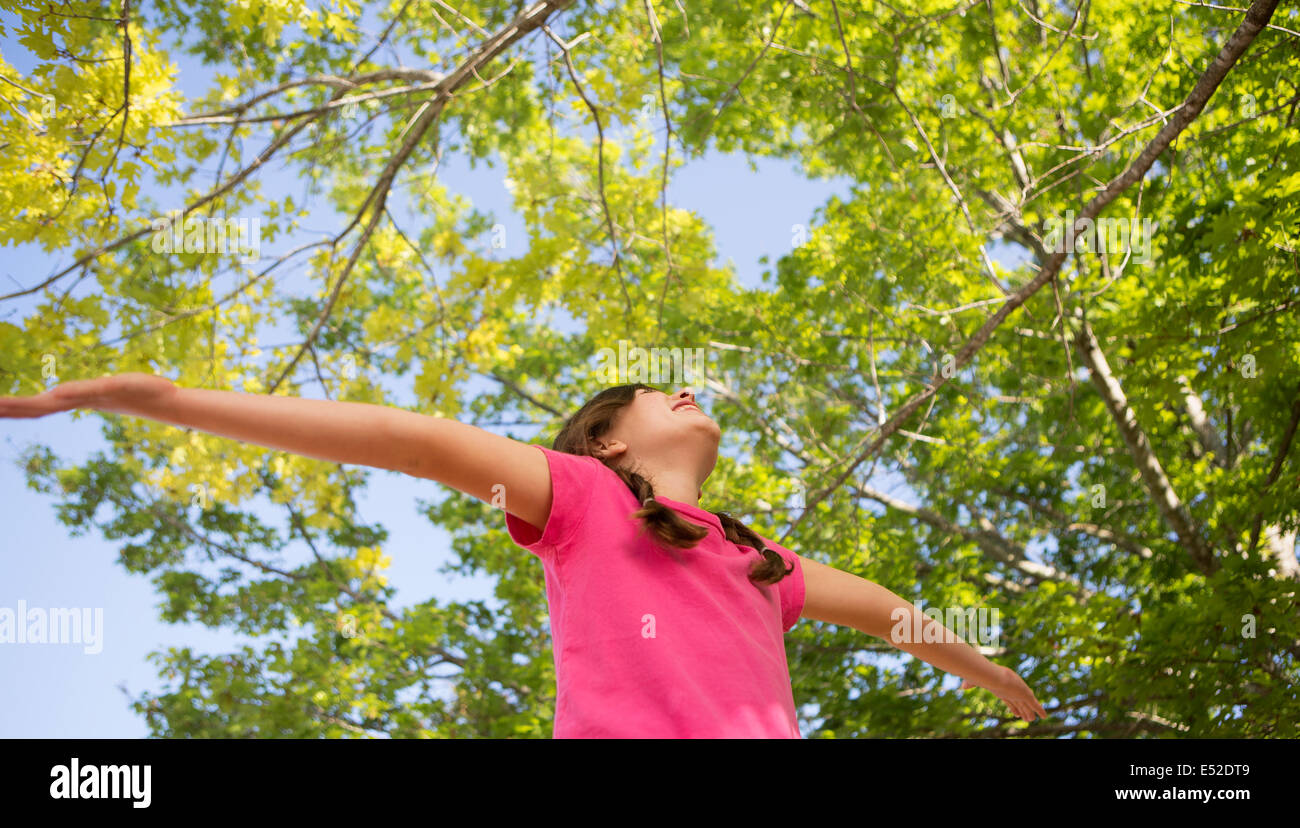 A young girl with braids wearing a pink top with her arms outstretched and head back. - Stock Image