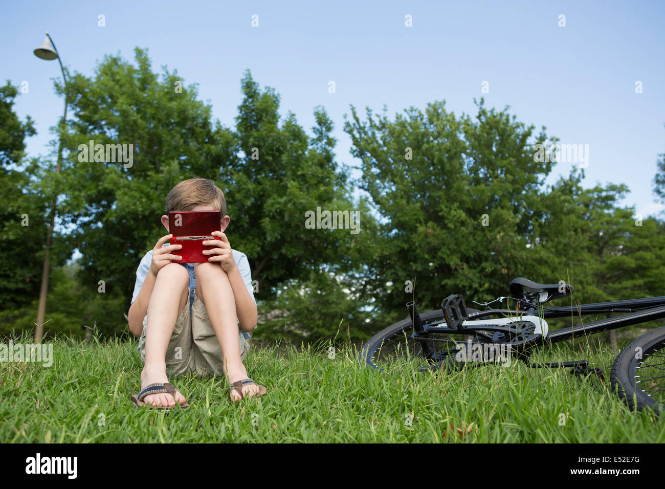A young boy sitting on the grass playing a hand held electronic game. Stock Photo