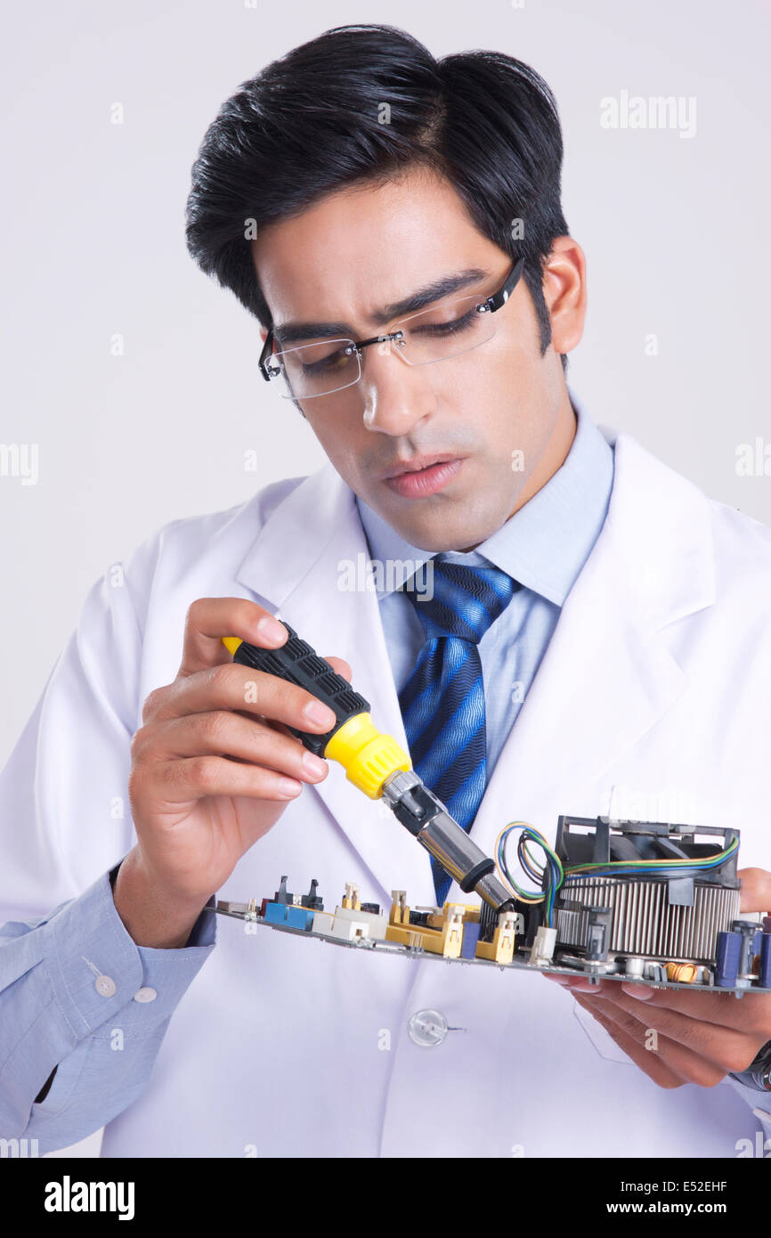 Young male technician working on machine part over gray background - Stock Image