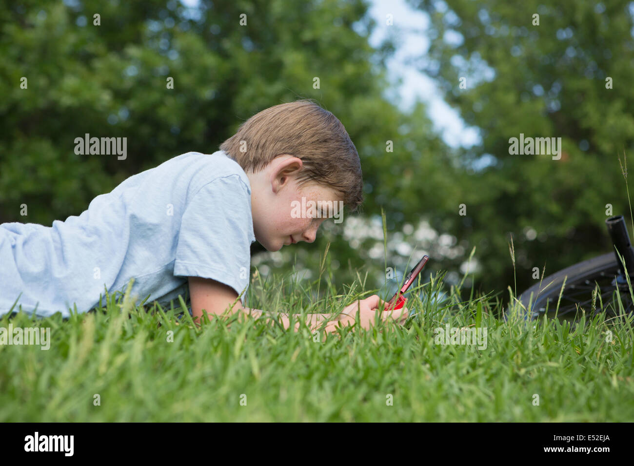 A young boy lying on the grass playing a hand held electronic game. Stock Photo