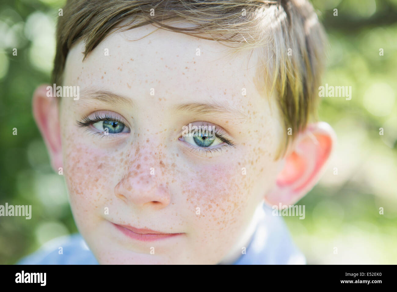 Portrait of a young boy with red hair, blue eyes and freckles on his nose. - Stock Image