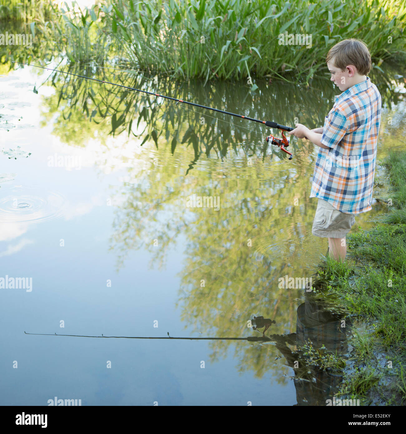 A young boy standing in water fishing with a rod. - Stock Image