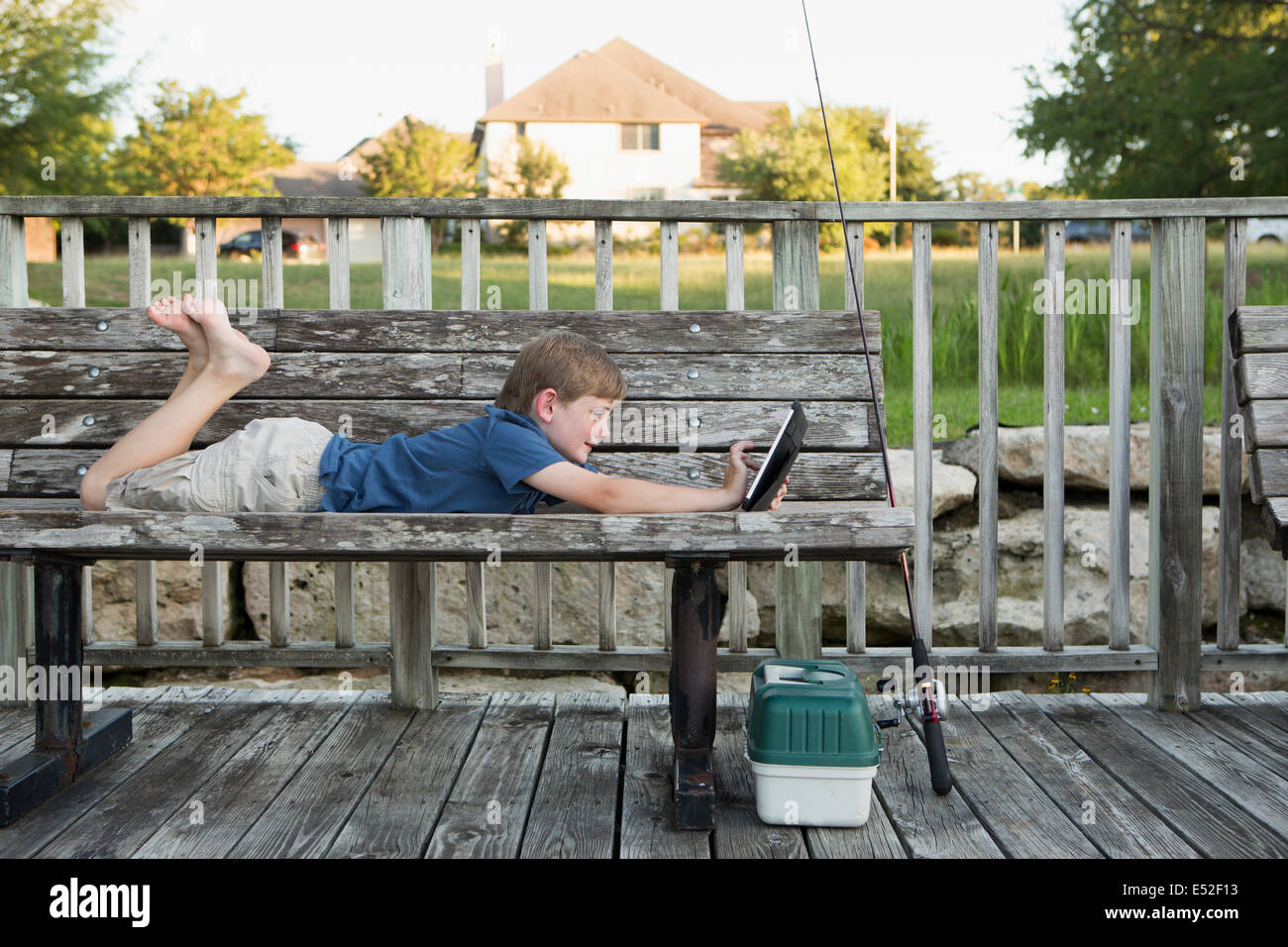 A young boy outdoors lying on a bench using a digital tablet. fishing equipment. Stock Photo