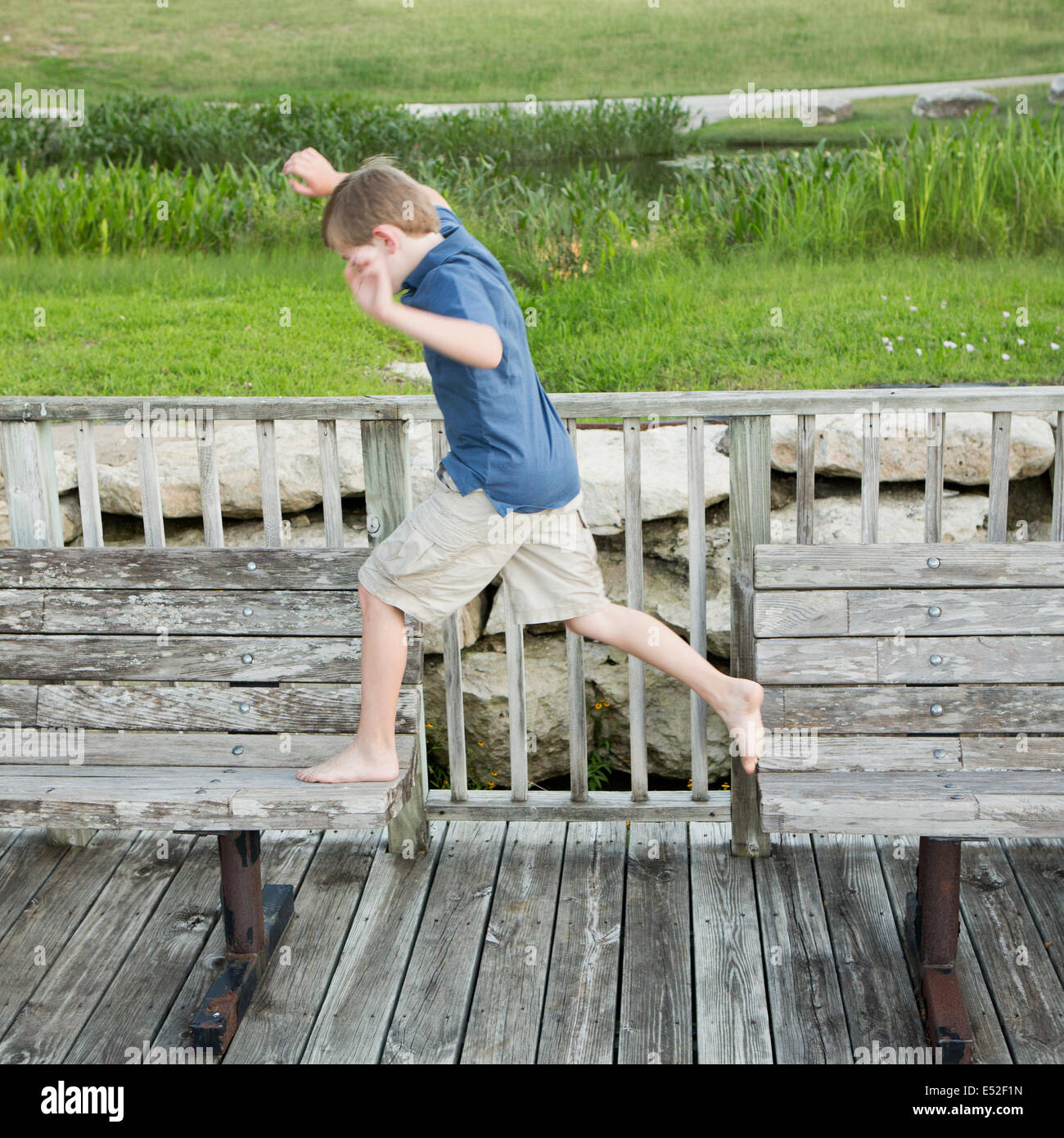 A young boy outdoors leaping from one bench to another on a jetty over water. - Stock Image