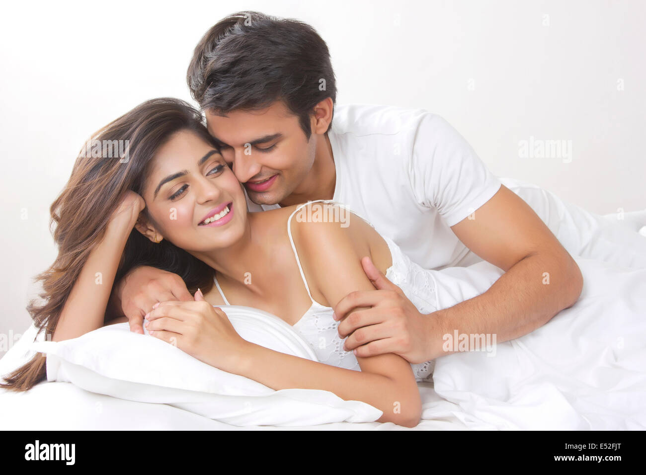 Romantic young couple in bedroom - Stock Image