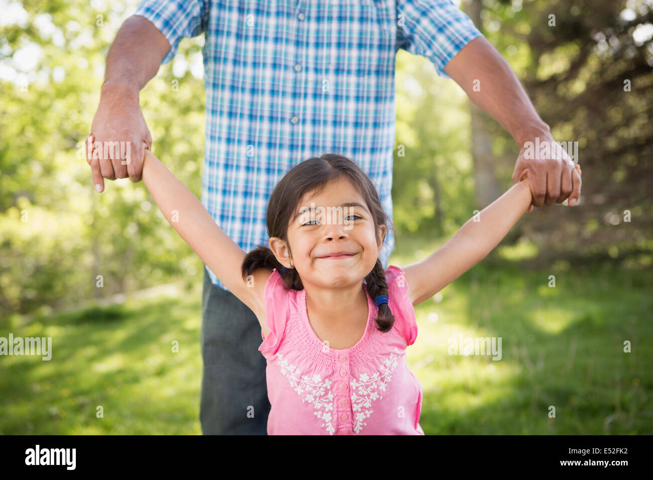 A young child in a pink dress with her arms outstretched playing with her father. - Stock Image