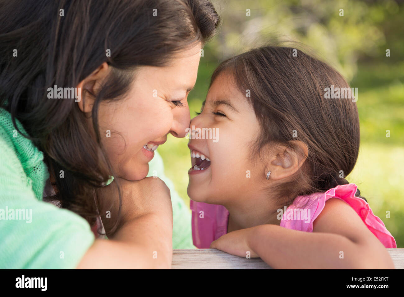 A mother in the park with her daughter, laughing and kissing each other. - Stock Image