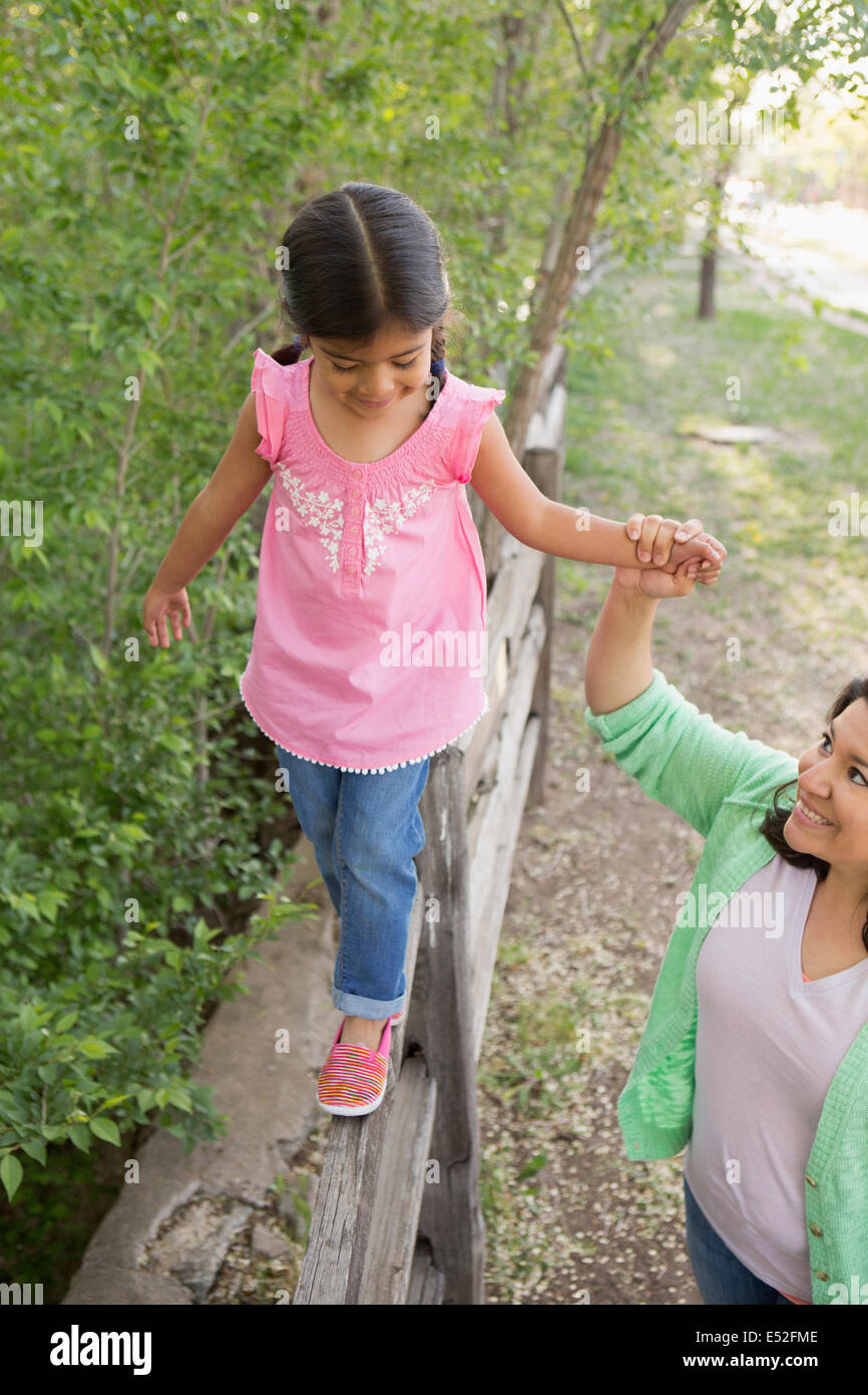 A young girl in a pink shirt and jeans, walking along a fence holding her mother's hand. - Stock Image