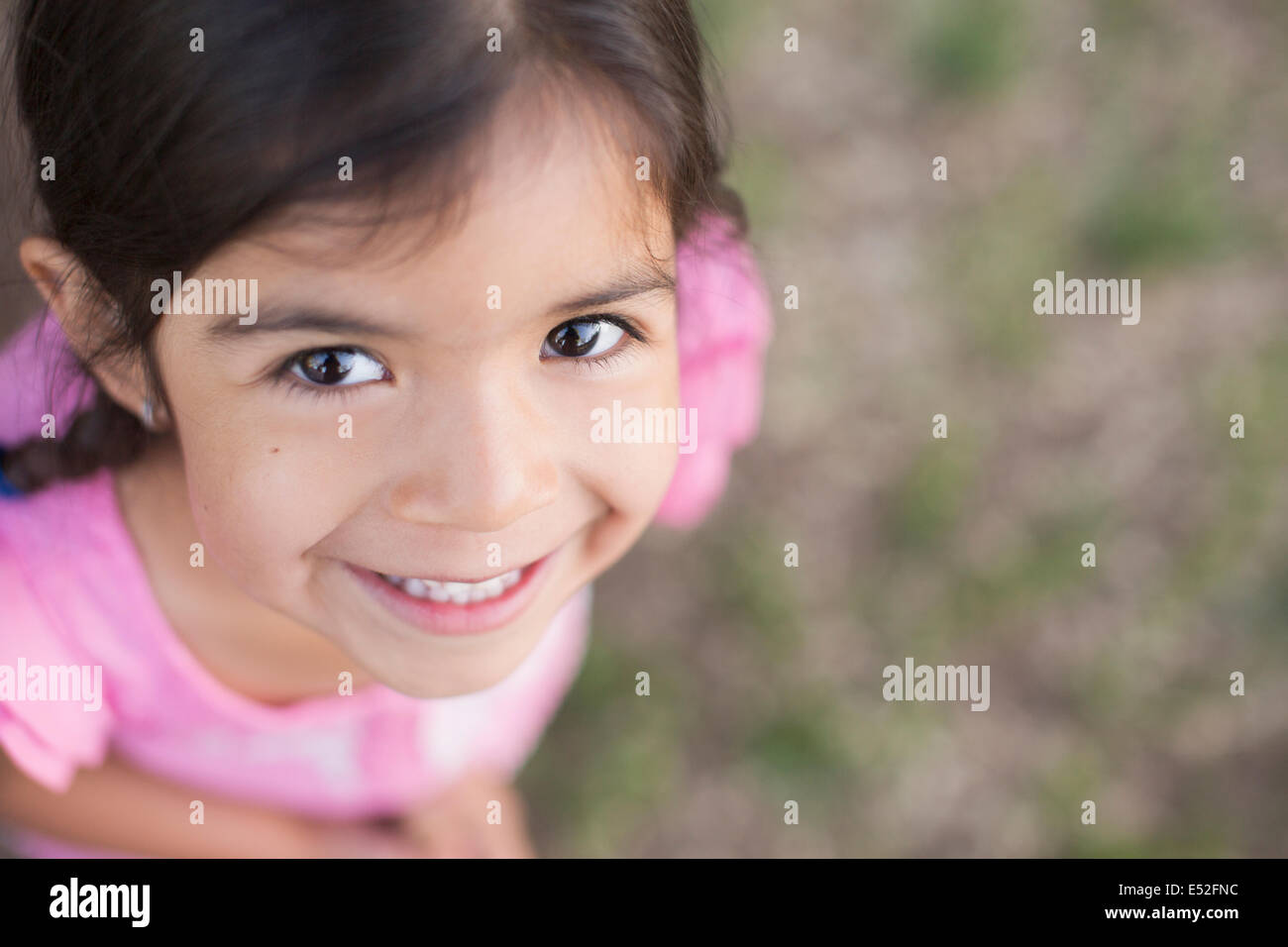 View from above of a child, a girl with dark brown hair and brown eyes. - Stock Image